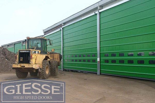Green industrial roller shutters warehouse in a farming setting with a tractor in the forefront