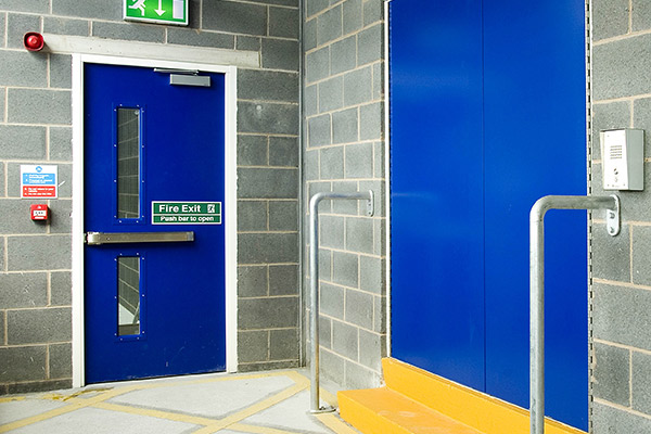 Blue emergency fire door with push bar, glass and warning stickers