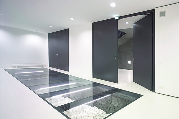 Metal secutiry doors in a glossy white hallway with a glass floor
