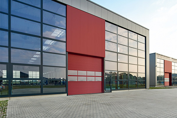 a red roller shutter installed on a large scale workshop with glass panes throughout