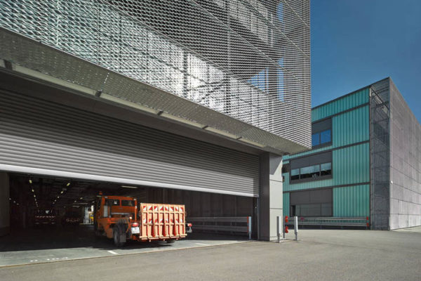 A large silver commercial roller shutter door half open