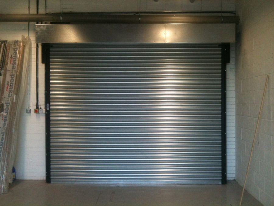 tall industrial grade fire protection shutters installed in a small warehouse